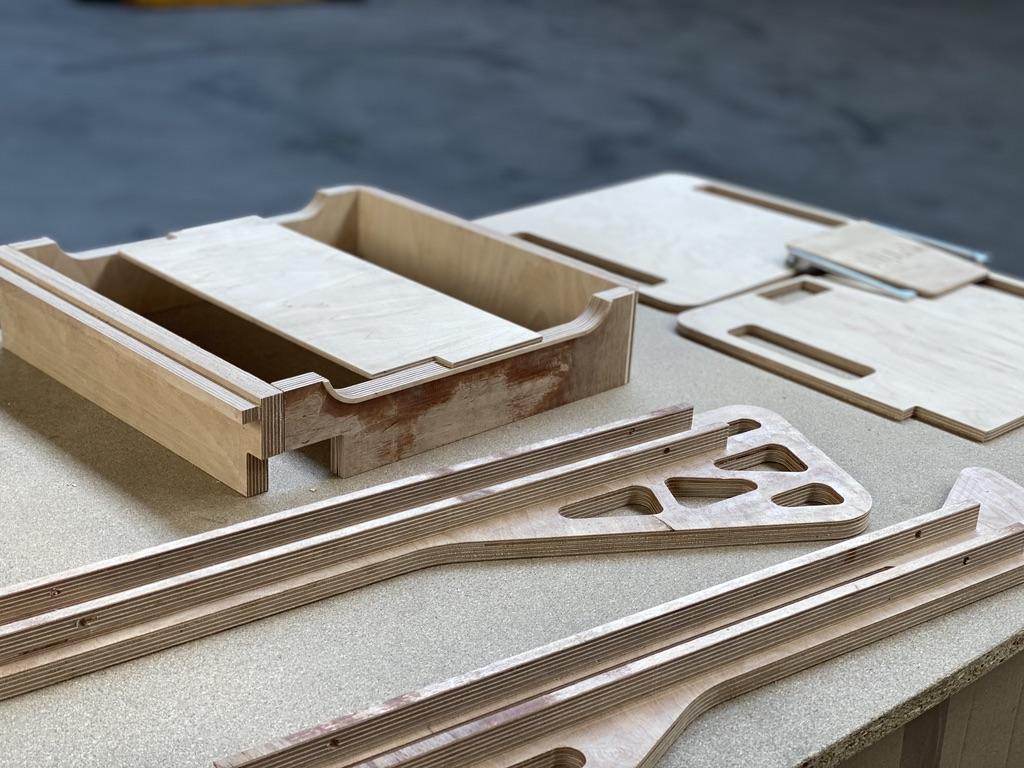 Divers usinages en bois en attente d'être monté avec d'autres pièces en tôlerie